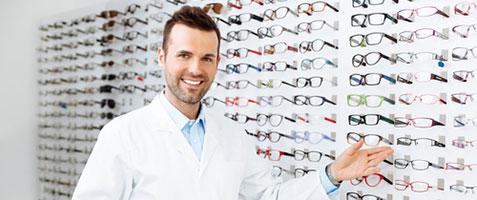 Opticien devant un panneau de lunettes optiques